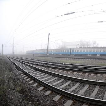De oekraïense trein in de voorsteden snelt langs de spoorweg in een mistige ochtend