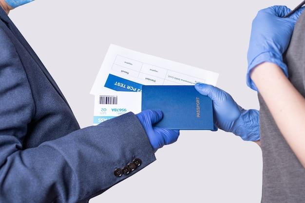 De officier neemt documenten van de passagier ter controle. paspoort, ticket, covid-19 pcr-test, close-up.