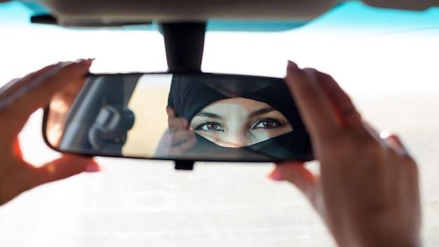De ogen van de moslimvrouw in de achteruitkijkspiegel van een auto.