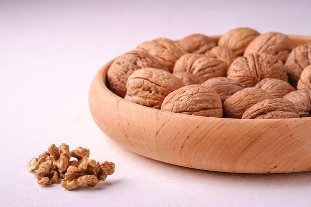 De okkernoten hopen voedsel in houten kom op witte achtergrond dichtbij aan gepelde noten, hoekmening, gezond voedselconcept op
