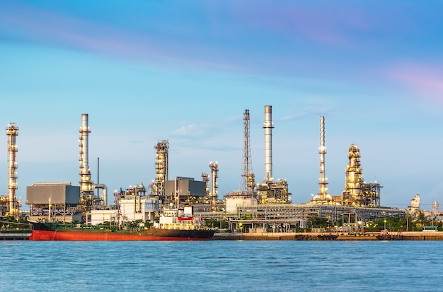 De olieraffinaderij aan de rivier in de schemering