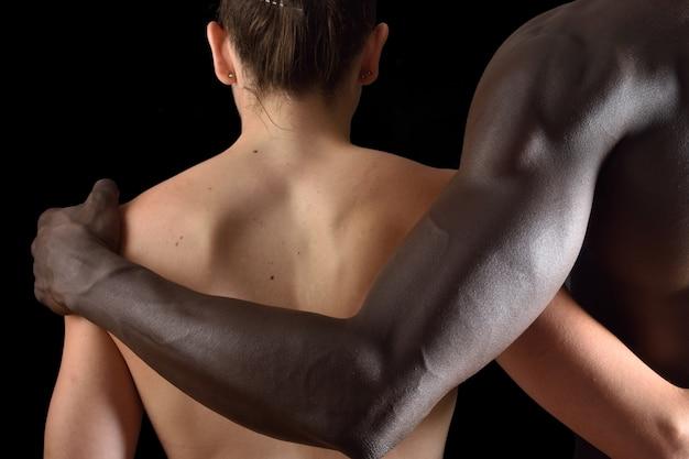 De omhelzing van een interraciaal paar op zwarte achtergrond