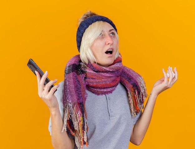 De onaangename jonge blonde zieke slavische vrouw die de wintermuts en sjaal draagt houdt telefoon vast