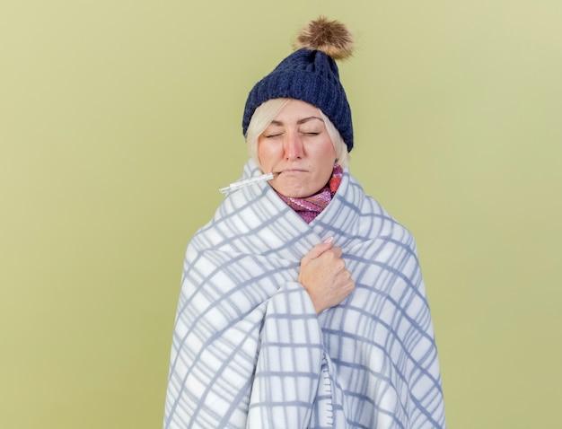 De onaangename jonge blonde zieke vrouw die de wintermuts en sjaal draagt die in plaid wordt verpakt houdt thermometer in mond die op olijfgroene muur wordt geïsoleerd