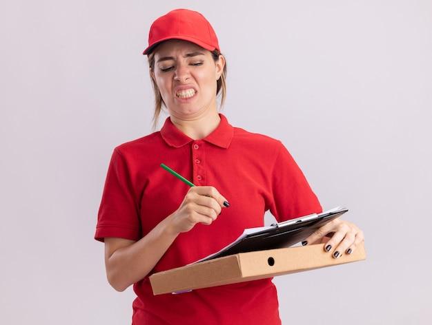 De onaangename jonge mooie leveringsvrouw in uniform houdt potlood en klembord op pizzadoos die op witte muur wordt geïsoleerd