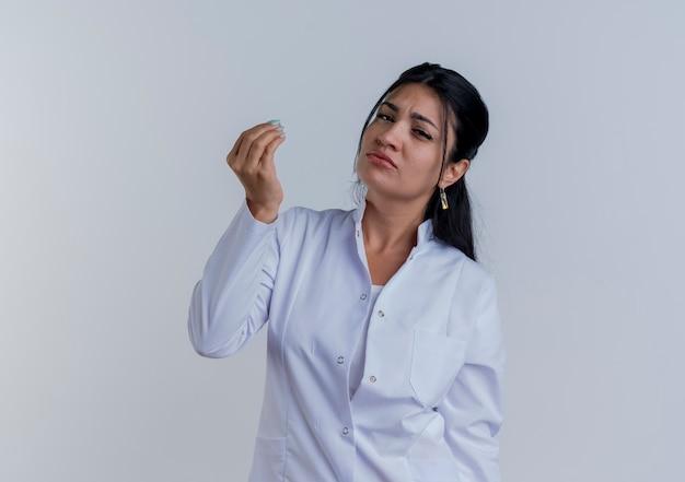 De onaangename jonge vrouwelijke arts die medische mantel draagt die het houden hand in lucht kijkt beweert iets geïsoleerd te houden