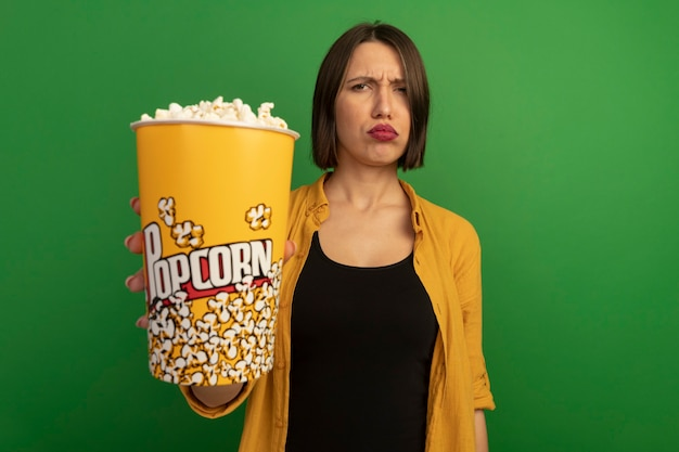 De onaangename mooie vrouw houdt emmer popcorn die op groene muur wordt geïsoleerd