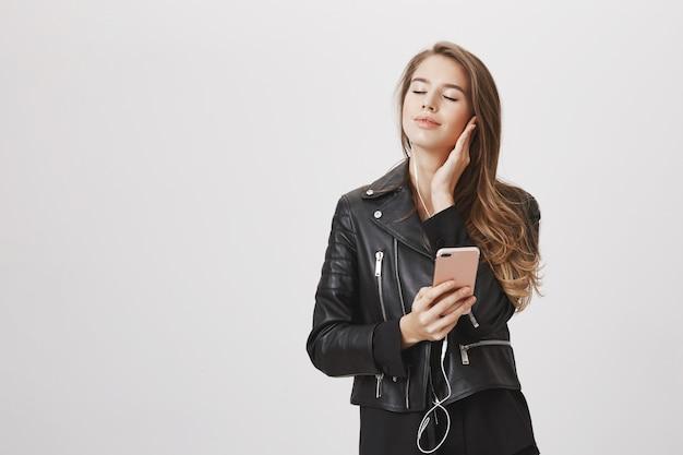 De onbezorgde vrouw sluit ogen en glimlacht aangezien het luisteren muziek in oortelefoons, mobiele telefoon houdt