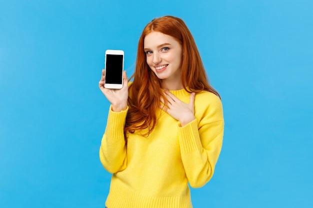 De onder de indruk en gefascineerde roodharige vrouw raakt haar hart en houdt een mobiel vast