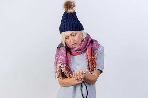 De onder de indruk jonge blonde zieke vrouw die de wintermuts en sjaal draagt, houdt een stethoscoop en kijkt naar de hand die op een witte muur wordt geïsoleerd