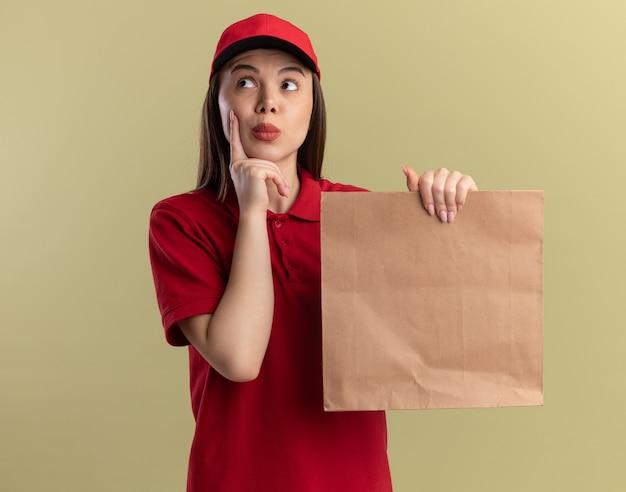 De onder de indruk mooie bezorgvrouw in uniform legt de vinger op het gezicht en houdt het papieren pakket vast, kijkend naar de zijkant op olijfgroen