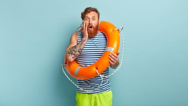 De onder de indruk zijnde roodharige man heeft een nerveuze gezichtsuitdrukking, is bang om voor het eerst in de oceaan te zwemmen en gebruikt een ringboei