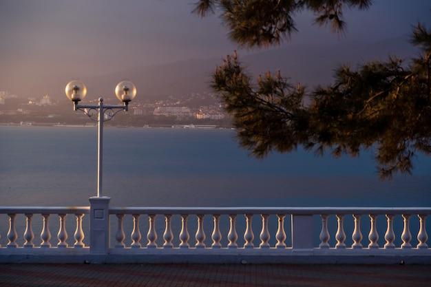 De ondergaande zon benadrukt heel mooi en contrasterend de balustrade van de dijk van de badplaats gelendzhik.