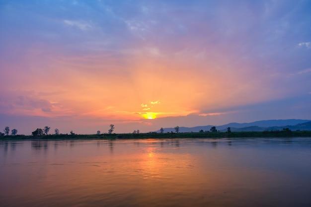 De ondergaande zon is blauw en oranje. mooie lucht in de avond bij de rivier