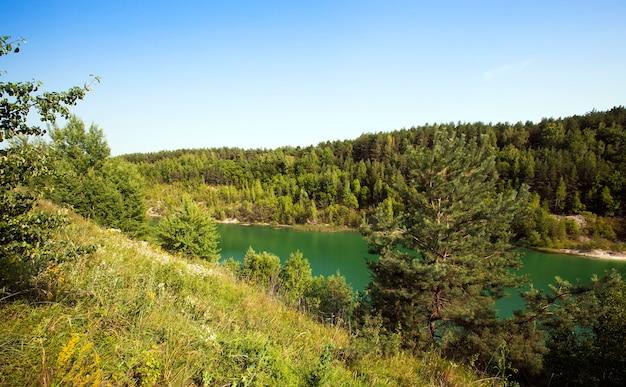 De ondergelopen putten met groen water. werden gevormd na krijtproductie. wit-rusland
