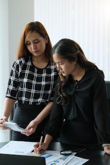 De onderneemster analyseert het doen van financiën en berekent op bureau over kosten op kantoor.