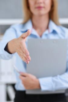 De onderneemster biedt hand aan als hallo in bureau te schudden