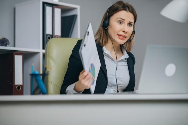 De onderneemster die in hoofdtelefoons door webcam bij webinar opleiding spreken bekijkt laptop