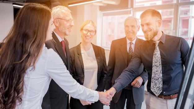 De onderneemster en de zakenman die elkaar schudden dienen de vergadering in