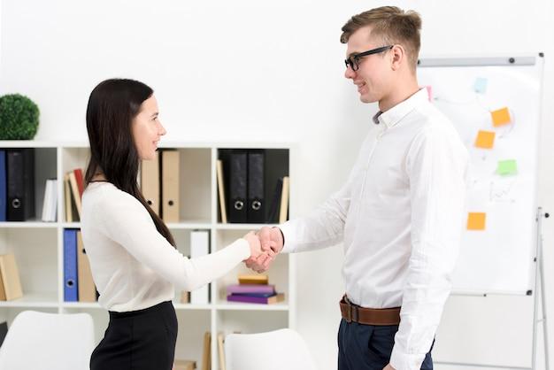 De onderneemster en de zakenman die elkaar schudden dienen het bureau in