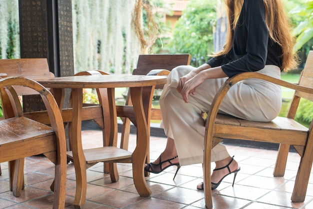 De onderste helft van lang haar jonge vrouwelijke benen in mode-stijl met hoge hak zitten op houten stoel in het midden van de tuin
