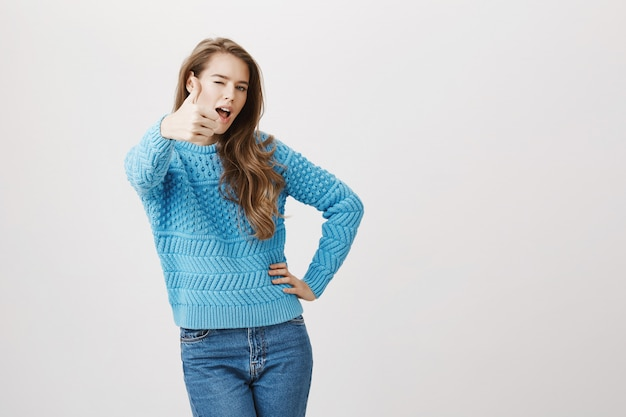 De ondersteunende aantrekkelijke vrouw toont duim-omhoog
