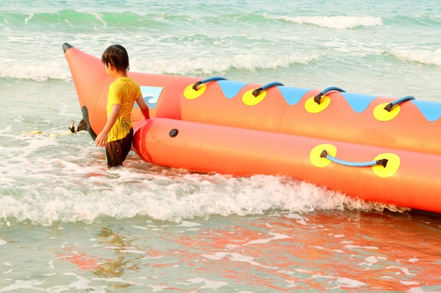 De onduidelijk beeldachtergrond van weinig jongen speelt banaanboot bij het overzees op de zomervakantie.