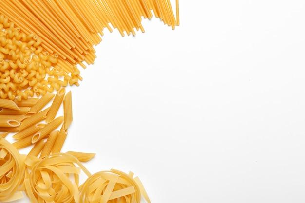 De ongekookte die macaroni van de deegwarenspaghetti op witte achtergrond wordt geïsoleerd