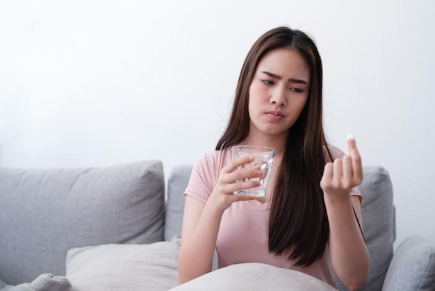 De ongelukkige zieke aziatische jonge drug van de vrouwenholding en glas waterpijnstiller om buikpijn te verlichten terwijl thuis het zitten op banklaag in woonkamer.
