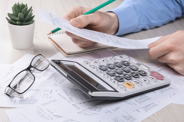 De onherkenbare zakenman gebruikend calculator op bureaukantoor en het schrijven maken nota met berekenen over kosten thuis kantoor.