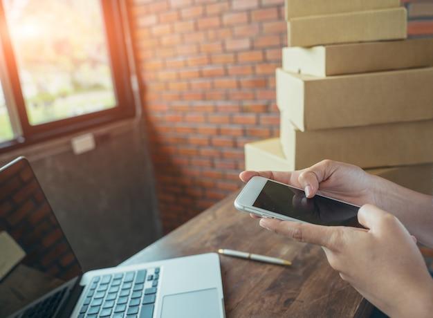 De online winkelende jongelui beginnen kleine onderneming in een kartondoos op het werk. de verkoper bereidt de leveringsdoos voor de klant, online verkoop of e-commerce voor., verkoopconcept.
