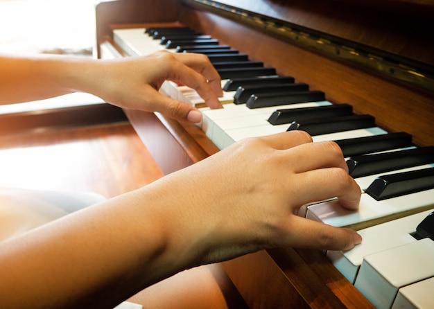 De onscherpe lichte ontwerpachtergrond van menselijke hand drukt op pianosleutel, warme lichte toon