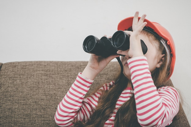 De ontdekkingsreiziger van het meisje kijkt door verrekijkers