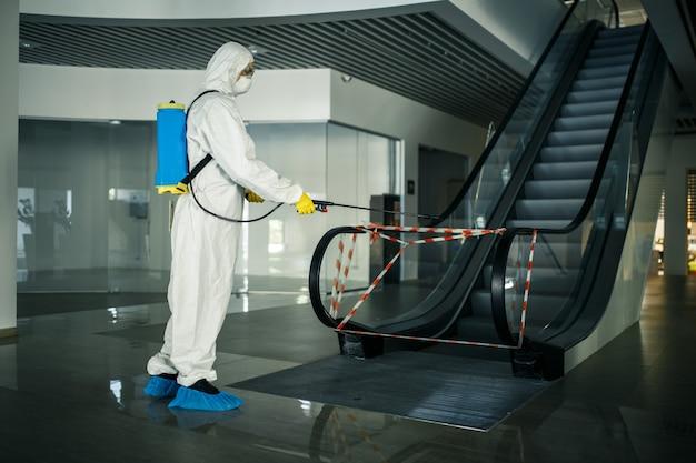 De ontsmettingsmedewerker desinfecteert de roltrap met een spray in het lege winkelcentrum om te voorkomen dat de covid-19 zich op openbare plaatsen verspreidt.