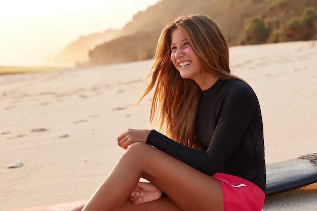 De ontspannen aantrekkelijke jonge ruiter van golven heeft een brede glimlach op het gezicht, terloops gekleed