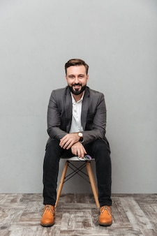De ontspannen gebaarde mensenzitting van gemiddelde lengte op stoel in bureau, en glimlachen op camera die over grijs wordt geïsoleerd