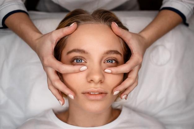 De ontspannen jonge vrouw kijkt omhoog. ze ligt op de bank. schoonheidsspecialiste geeft haar gezichtsmassage met blote handen. gevoelig en goed gevoel.