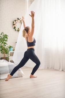 De ontspannen vrouw doet sportoefeningen thuis in sportkleding. ochtendoefening.