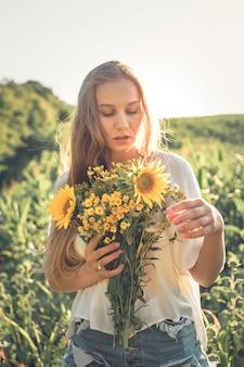 De ontspannende jonge vrouw met vermindert in aard, in graan, zonnebloemgebied