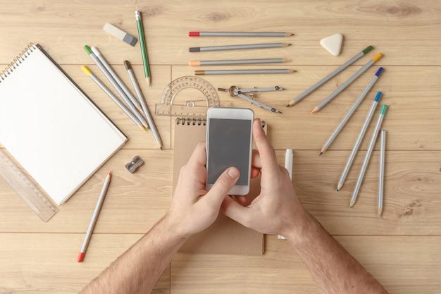 De ontwerper tekent een schets in een notitieblok op een houten tafel. briefpapier. uitzicht van boven.