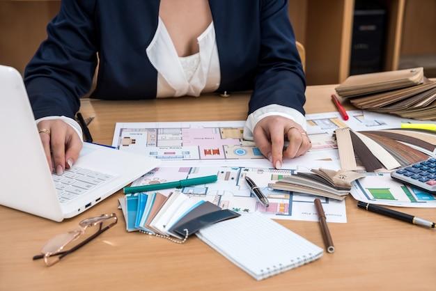 De ontwerper werkt op kantoor met kleurstalen, een laptop en een plattegrond van het gebouw