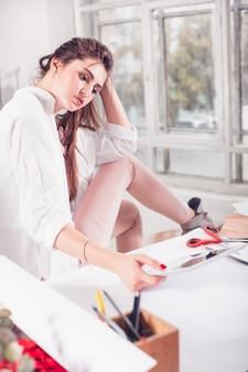 De ontwerpervrouw die van de manier in studiozitting aan het bureau werkt