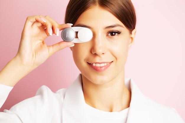 De oogarts houdt een bakje met contactlenzen bij de ogen