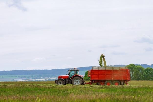 De oogstmachine verzamelt vers gemaaid gras in een trekkeroplegger voor transport.