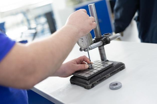 De operator voert de controle over metalen details uit