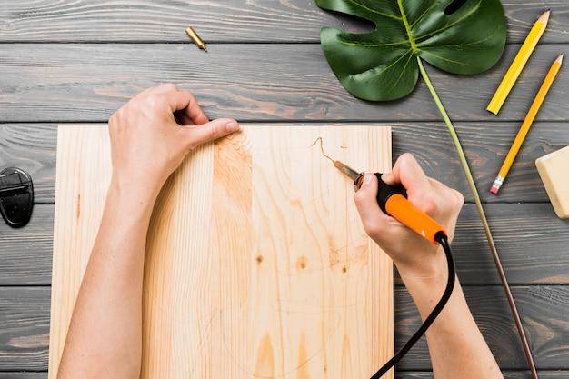 De opgeheven mening van hand snijdt harde houten raad op bureau