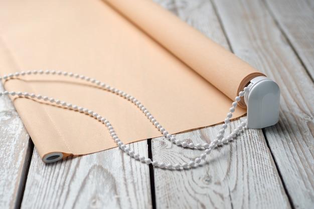 De opgerolde beige luiken staan op een houten ondergrond. beige jaloezieën liggen op een oude houten witte tafel.
