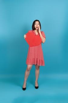 De opgewekte jonge aziatische vrouw van gemiddelde lengte die met open mond in rode kleding groot rood document hart houden