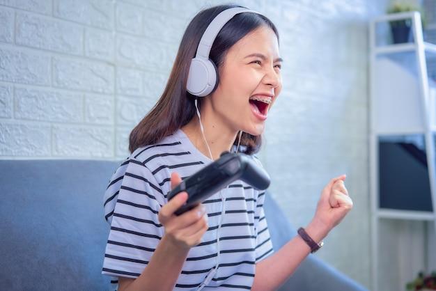 De opgewekte jonge aziatische vrouwenzitting op bank draagt witte hoofdtelefoon op het hoofd en thuis het spelen van spelen in de woonkamer.