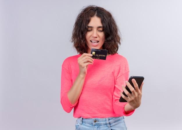 De opgewekte jonge mooie kaart van de vrouwenholding en mobiele telefoon op geïsoleerde witte muur met exemplaarruimte